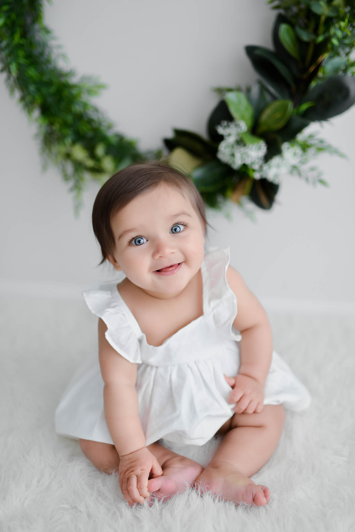 Baby in white Country Road summer dress smiling at camera with christmas wreath in background