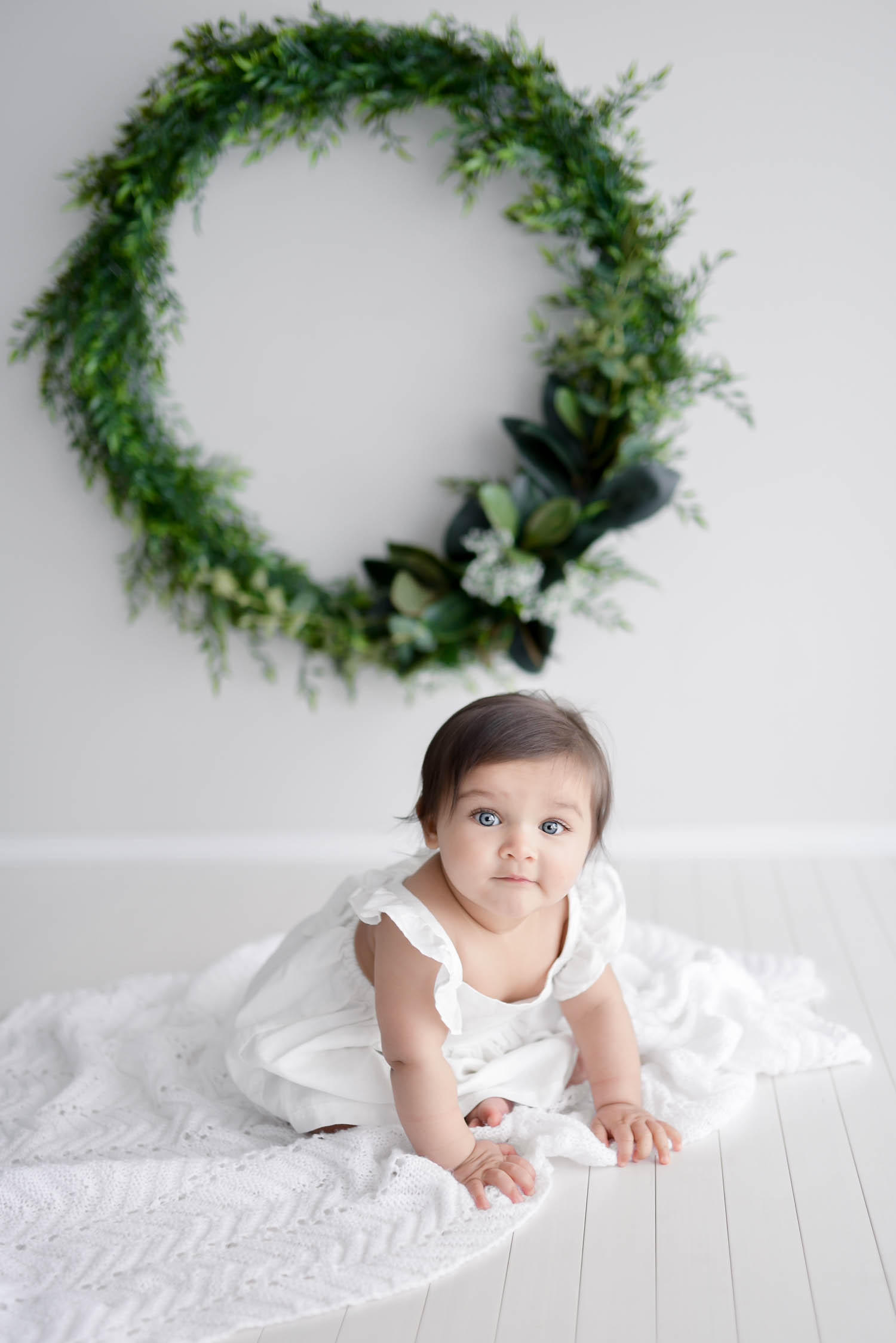 Baby sitting on white blanket wearing white dress Christmas wreath in background