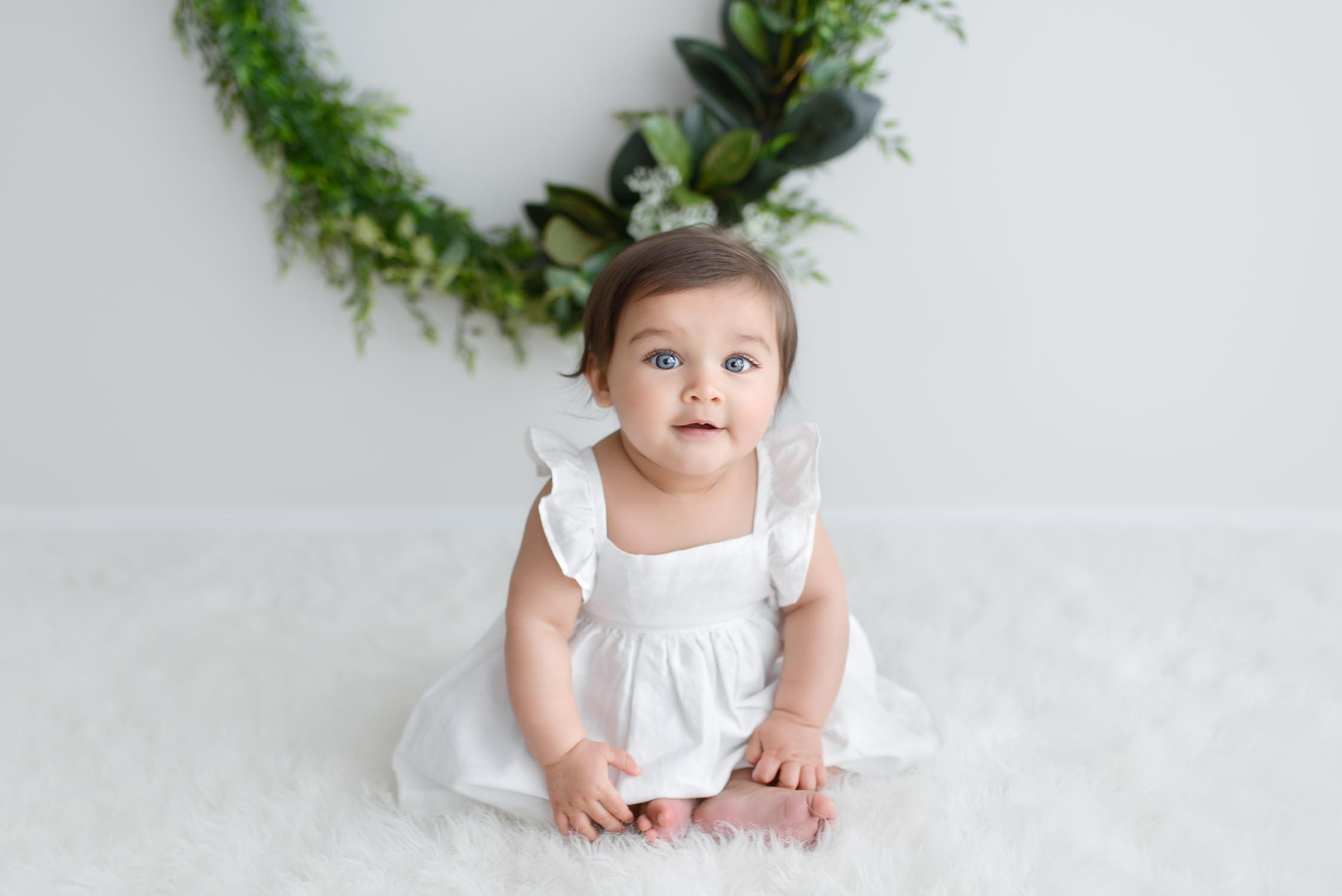 Baby in white Country Road summer dress looking at camera with christmas wreath in background