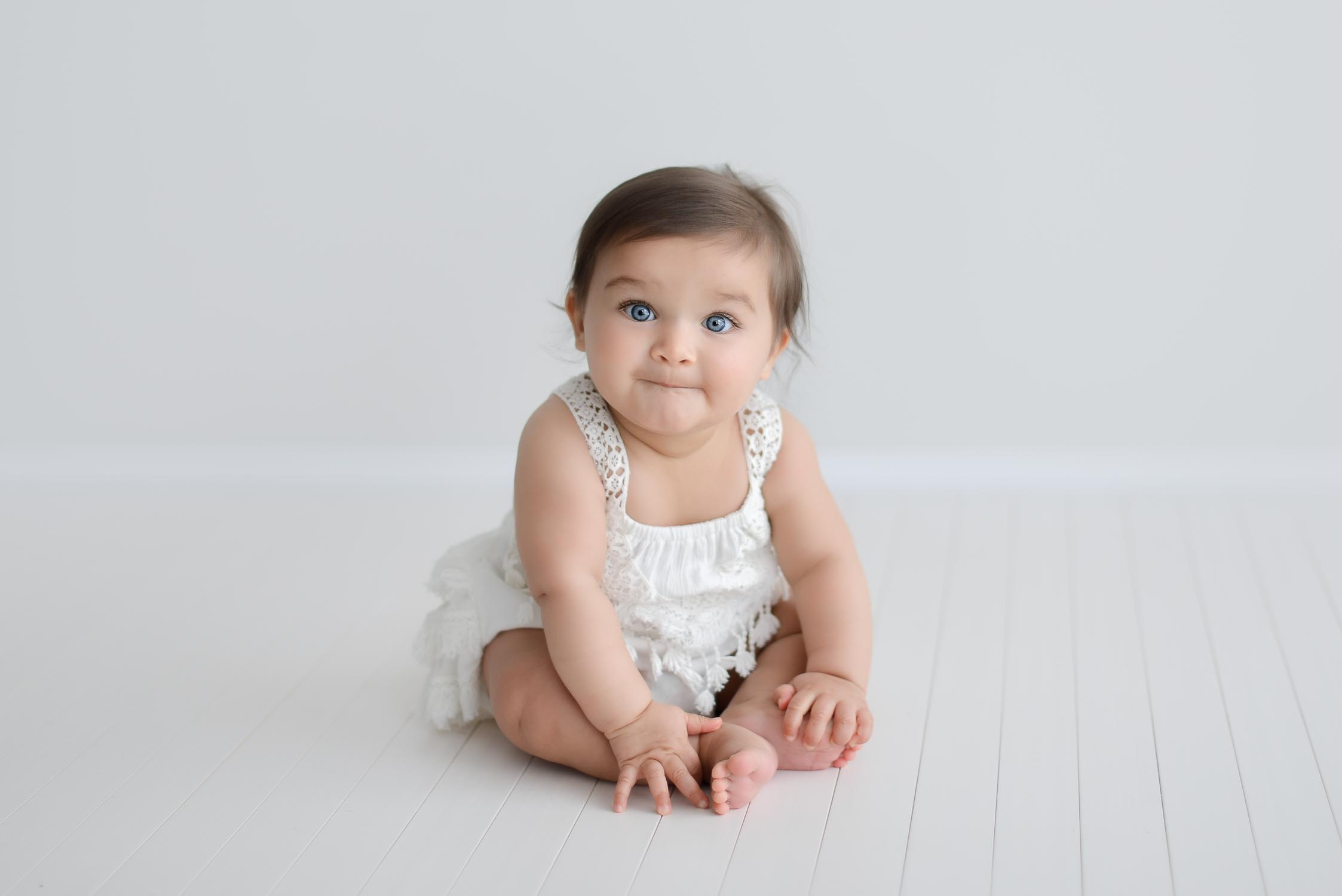 young baby sitting in natural light studio holding toes wearing white romper