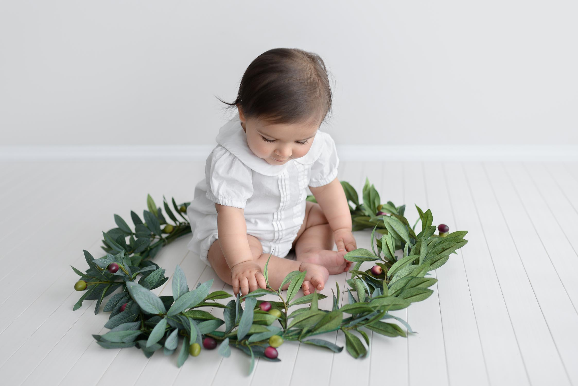 Baby sitting in christmas wreath in baby photography studio looking at wreath
