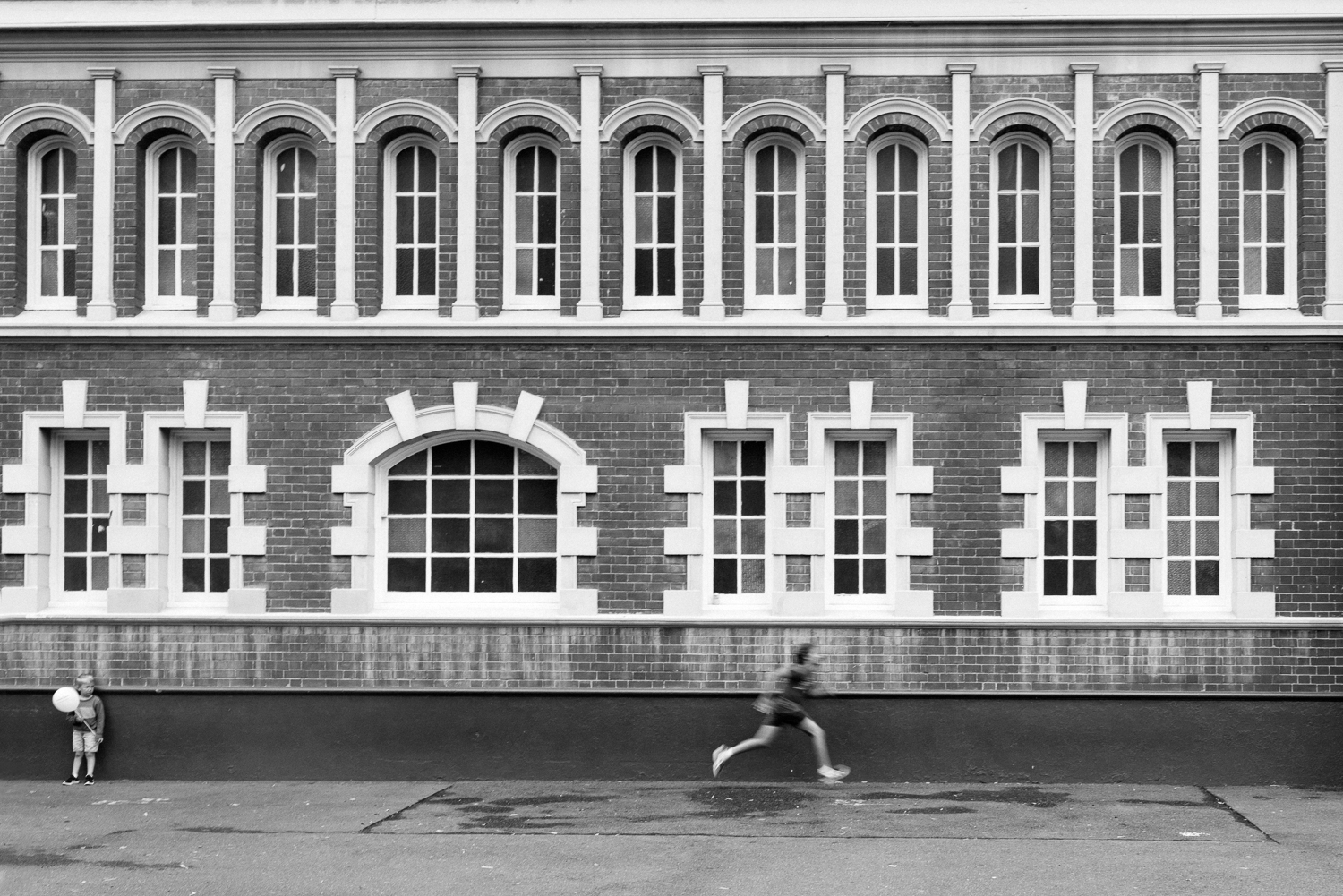 black and white photo of young boy running with old heritage building in background