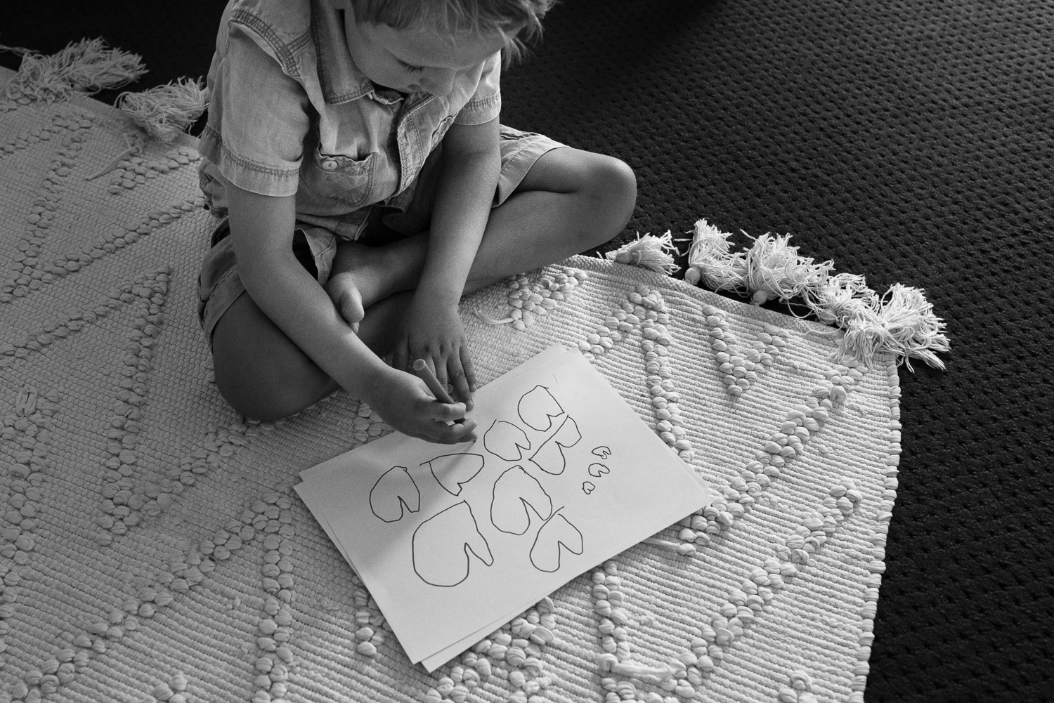 black and white image of young boy sitting cross legged on white rug learning to draw heart shapes on paper