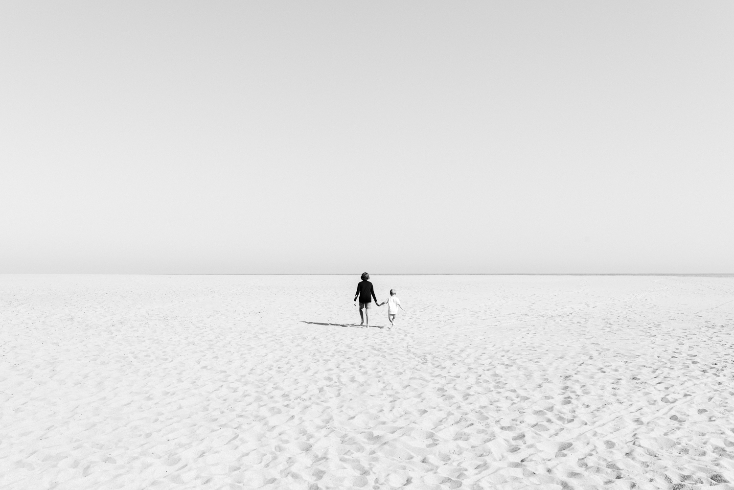 Black and white image of two young brothers walking on vast beach with only horizon in distance for children's photography photoshoot in Sutherland Shire Sydney