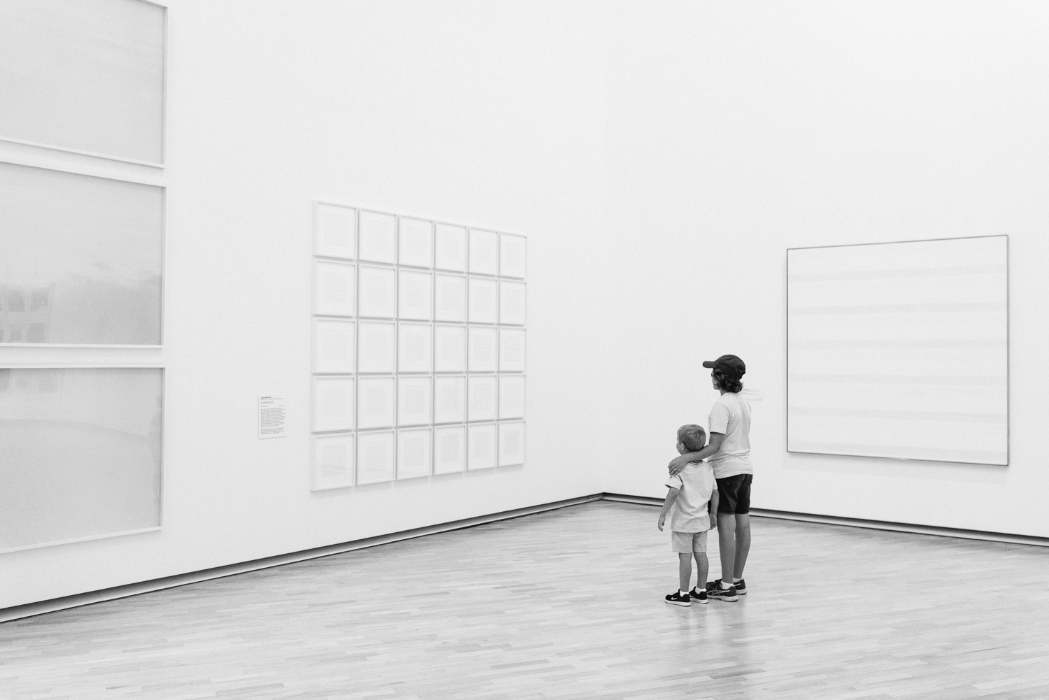Two young brothers looking at a wall of white blank artwork in art gallery