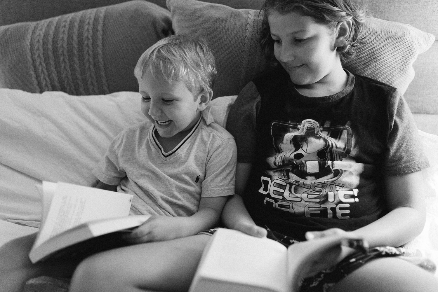Black and white image of two young brothers reading books together in bed