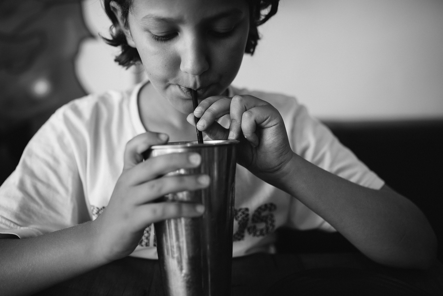 Young boy drinking milkshake in old fashioned milkshake metal cup