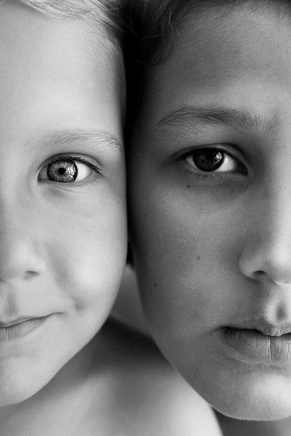 black and white image closeup of two brothers faces cropped on half of each face in natural light baby and children's portrait photography studio in the Sutherland Shire Sydney