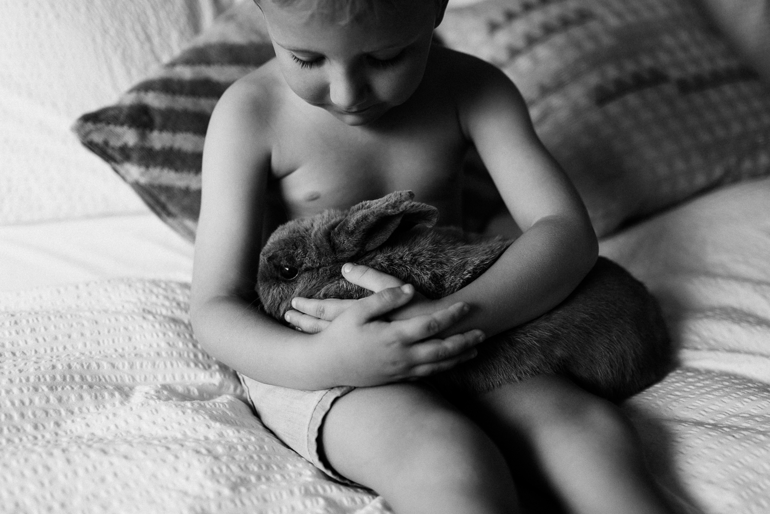 black and white image of young boy sitting on bed cuddling with pet rabbit