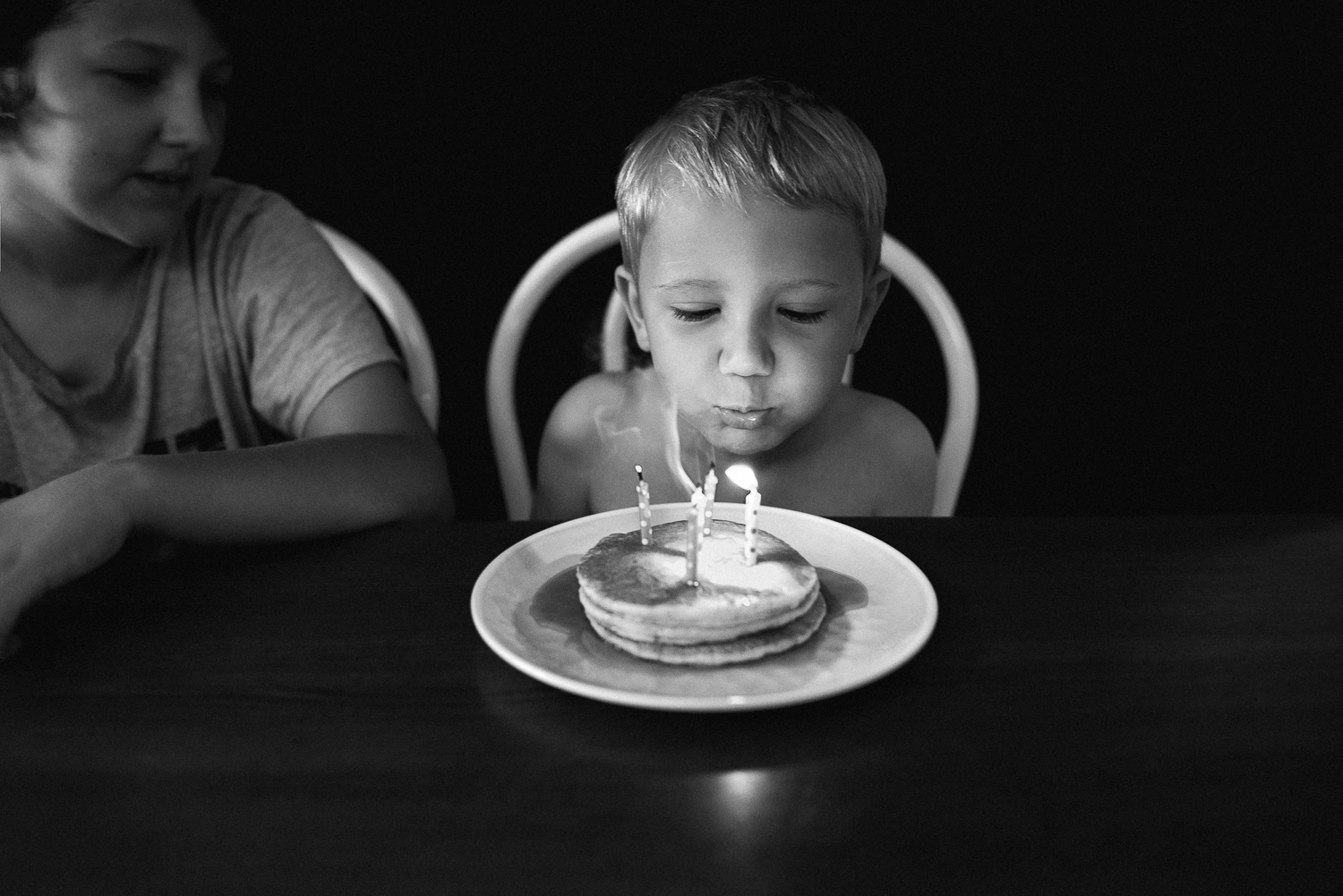 black and white image of young boy blowing out five birthday candles on a stack of pancakes with his older brother looking on from the side
