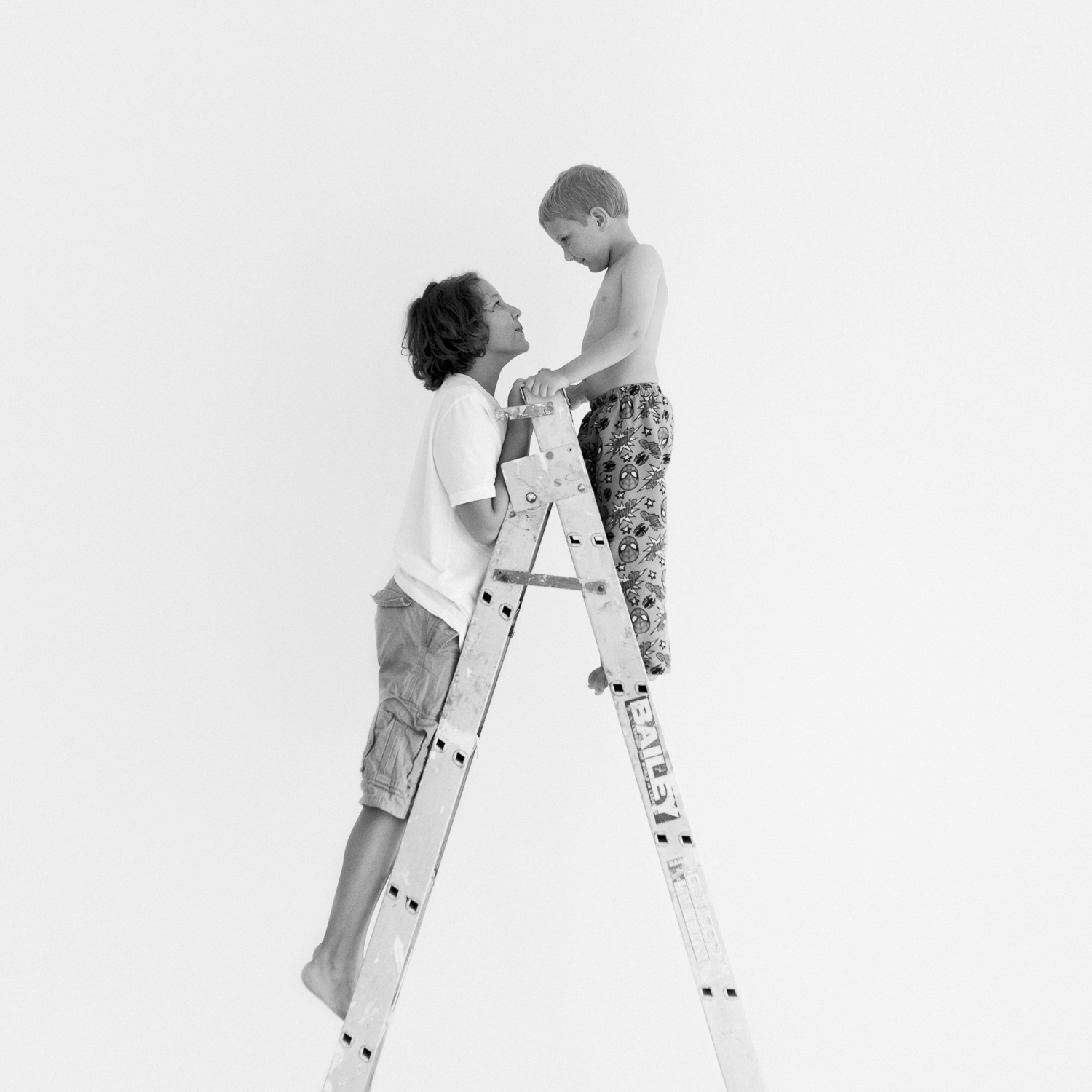 black and white image of two young boys on ladder in natural light children's photography studio sutherland shire Sydney