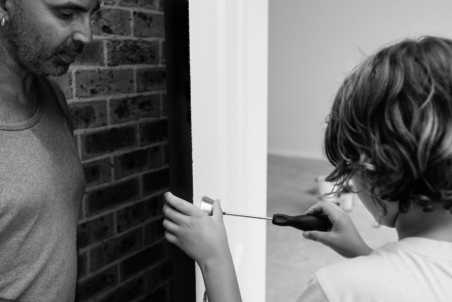 black and white image of father teaching young son how to fix a door