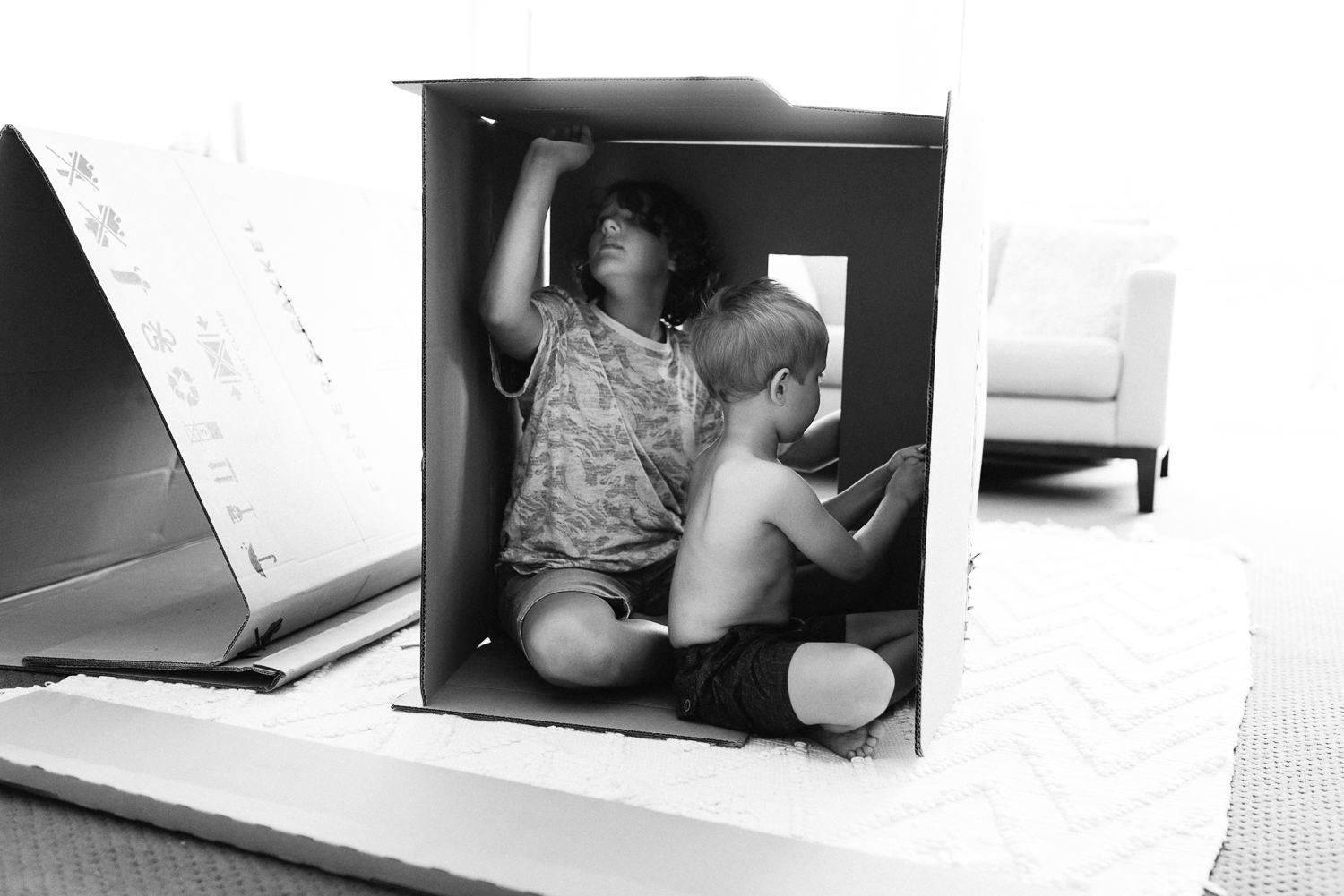 black and white photo of two young boys building cardboard box forts