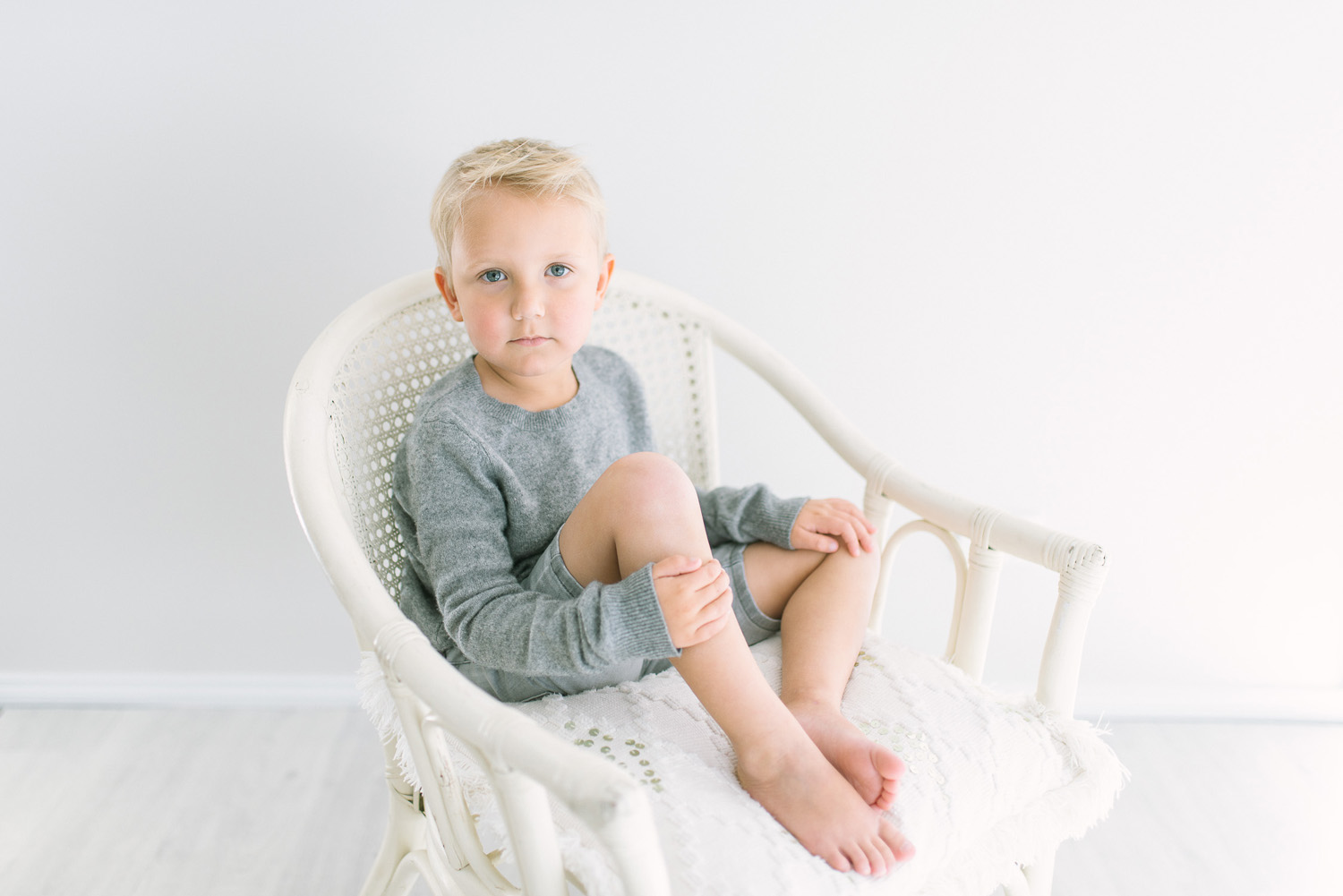 Young blond haired boy sitting on white cane chair during children's photography session in Sutherland Shire Baby and children's photography Studio in Sutherland Shire Sydney