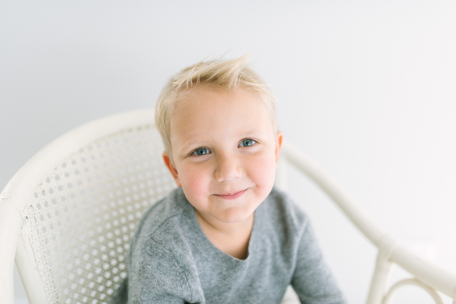 Young blond haired boy sitting on white cane chair smiling at camera during children's photography session in Sutherland Shire Baby and children's photography Studio in Sutherland Shire Sydney