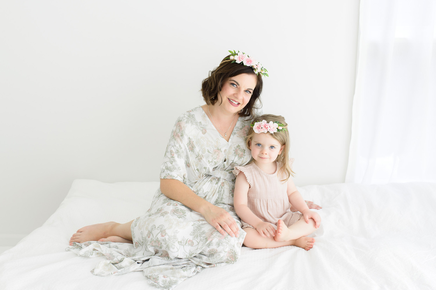 Mother and daughter sitting on bed wearing flower crowns and smiling at camera during sutherland shire baby photography session in Sevenish Photography studio
