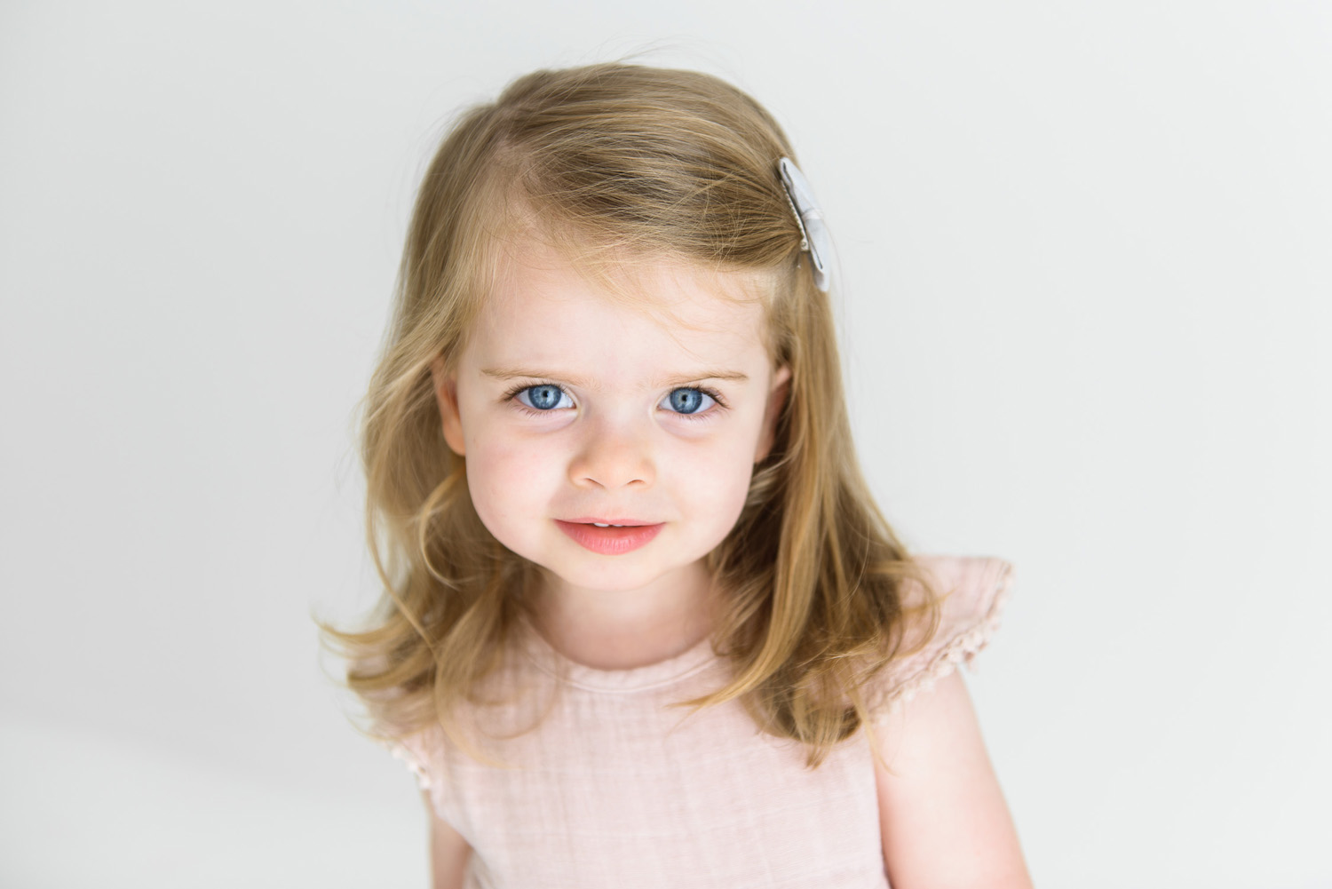Young girl smiling coyly at camera during sutherland shire baby photography session in Sevenish Photography Studio