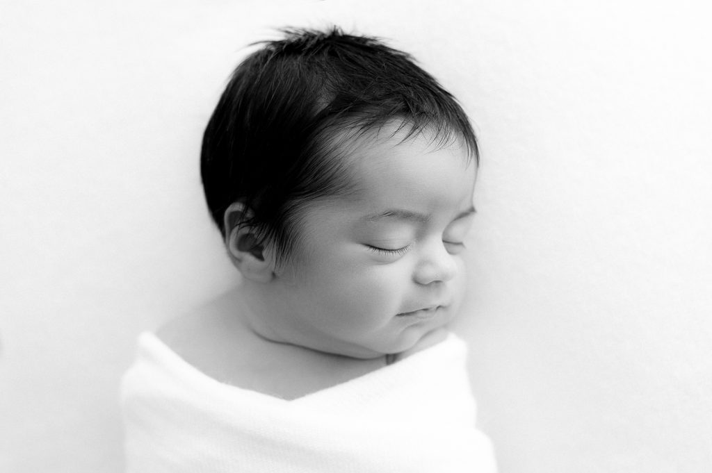 Black and white image of closeup of newborn baby's face side profile as they sleep as photographed by Sutherland Shire Newborn Photographer Sevenish Photography