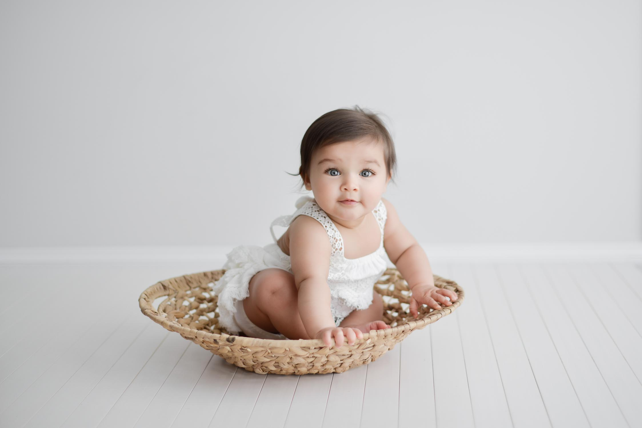 young baby sitting in shallow basket in photography studio looking at camera