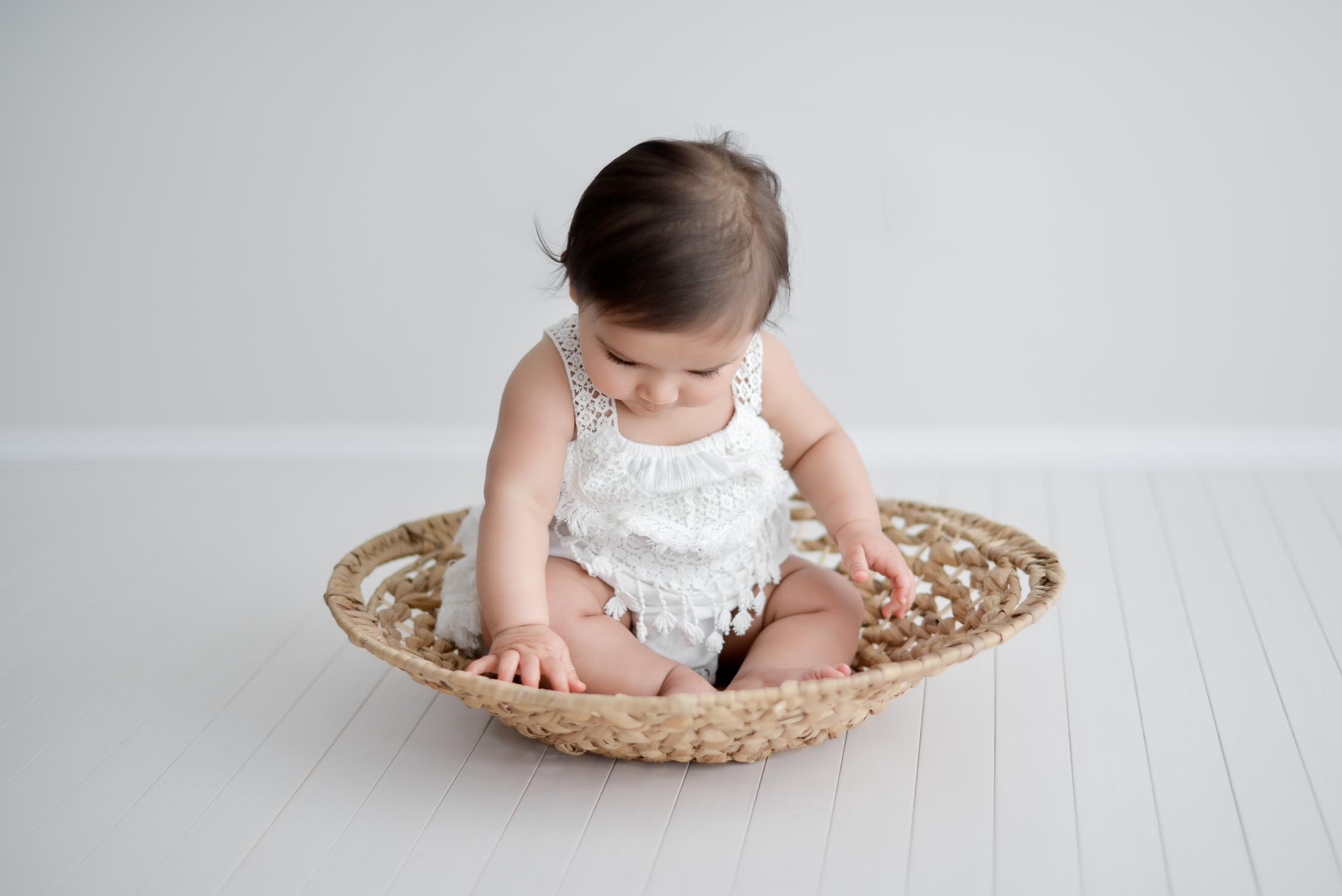 young baby sitting in shallow basket looking down