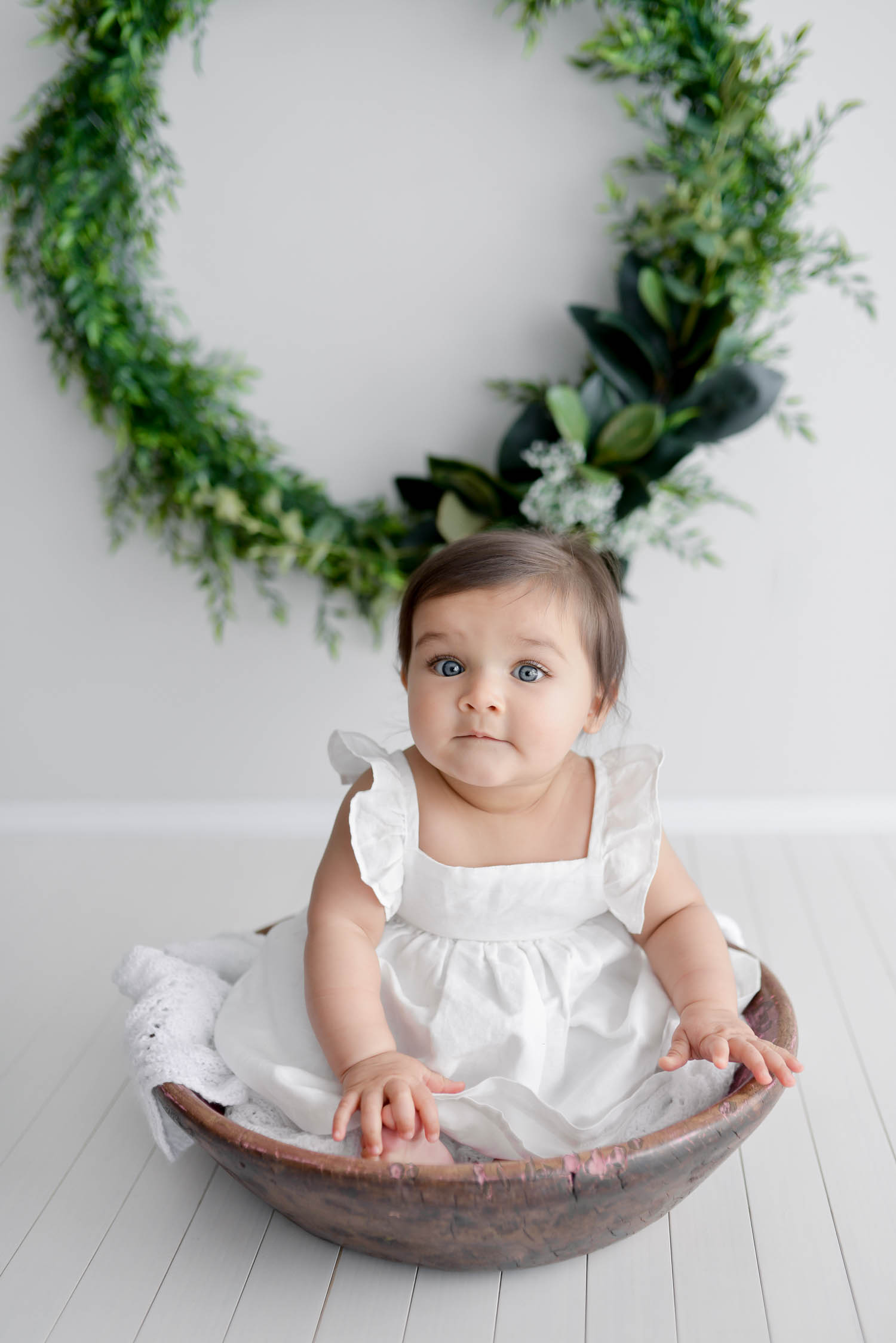 Baby sitting in bowl in white dress with christmas wreath in background
