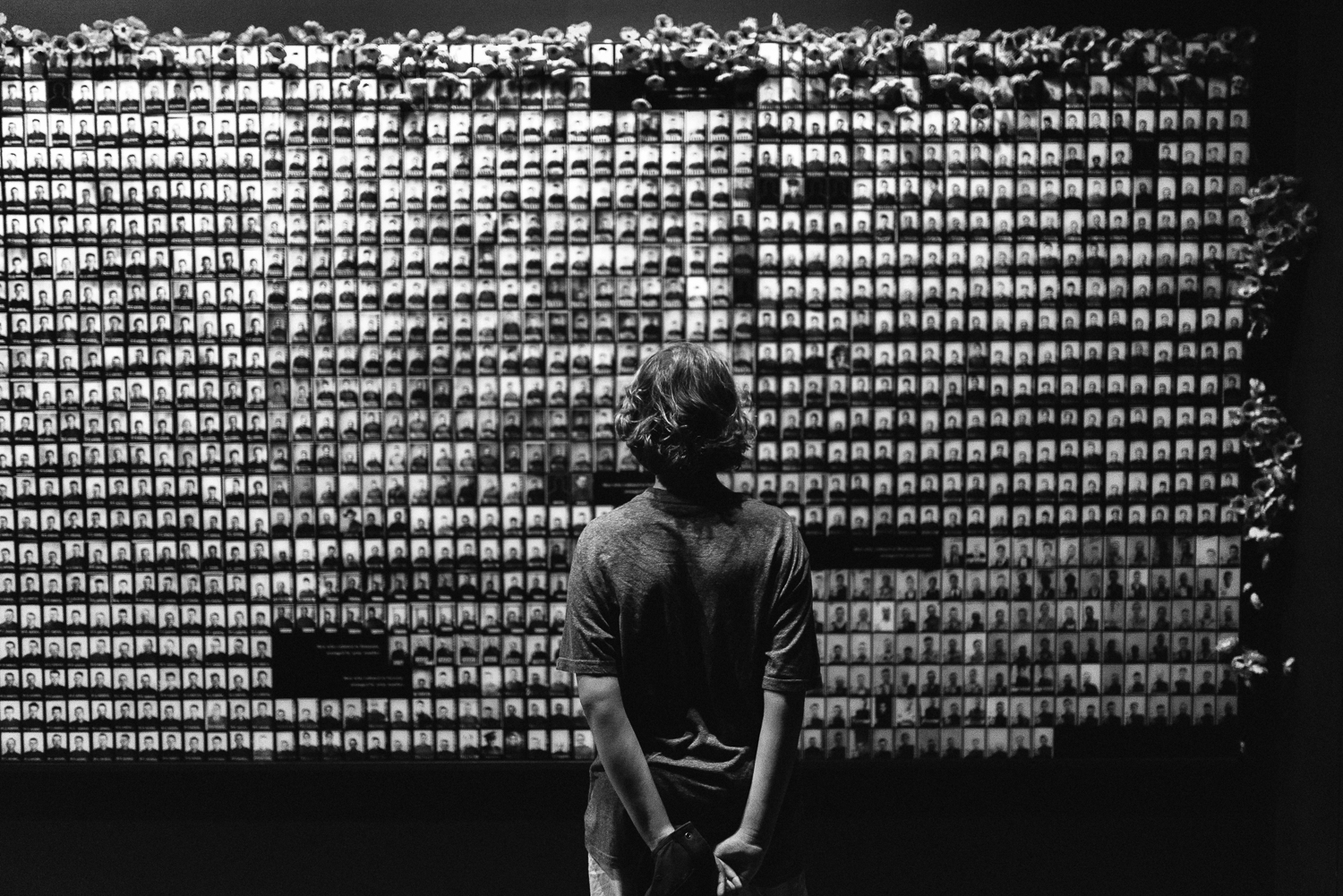Black and white image of young boy facing forward looking at hundreds of photos of soldiers that have died in war on wall at Australian War Memorial Canberra