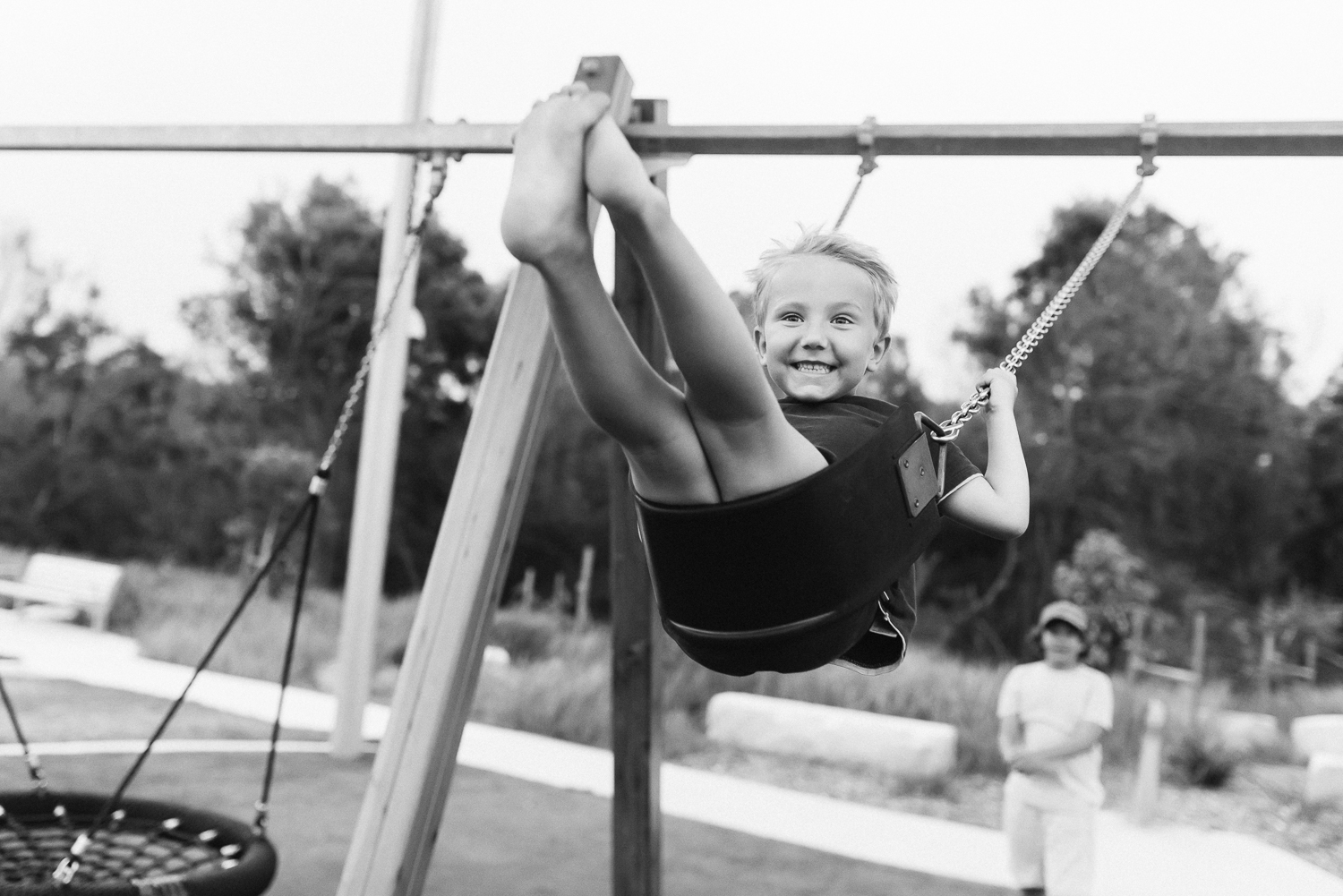 Black and white image of young boy on swing smiling swinging high up in the air with big brother looking on and pushing him at playground in Sutherland Shire Sydney