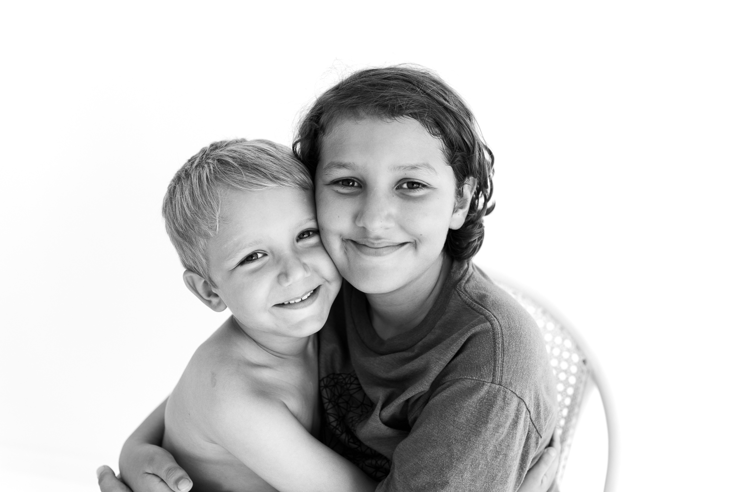 Black and white image of two brothers close up smiling and hugging each other