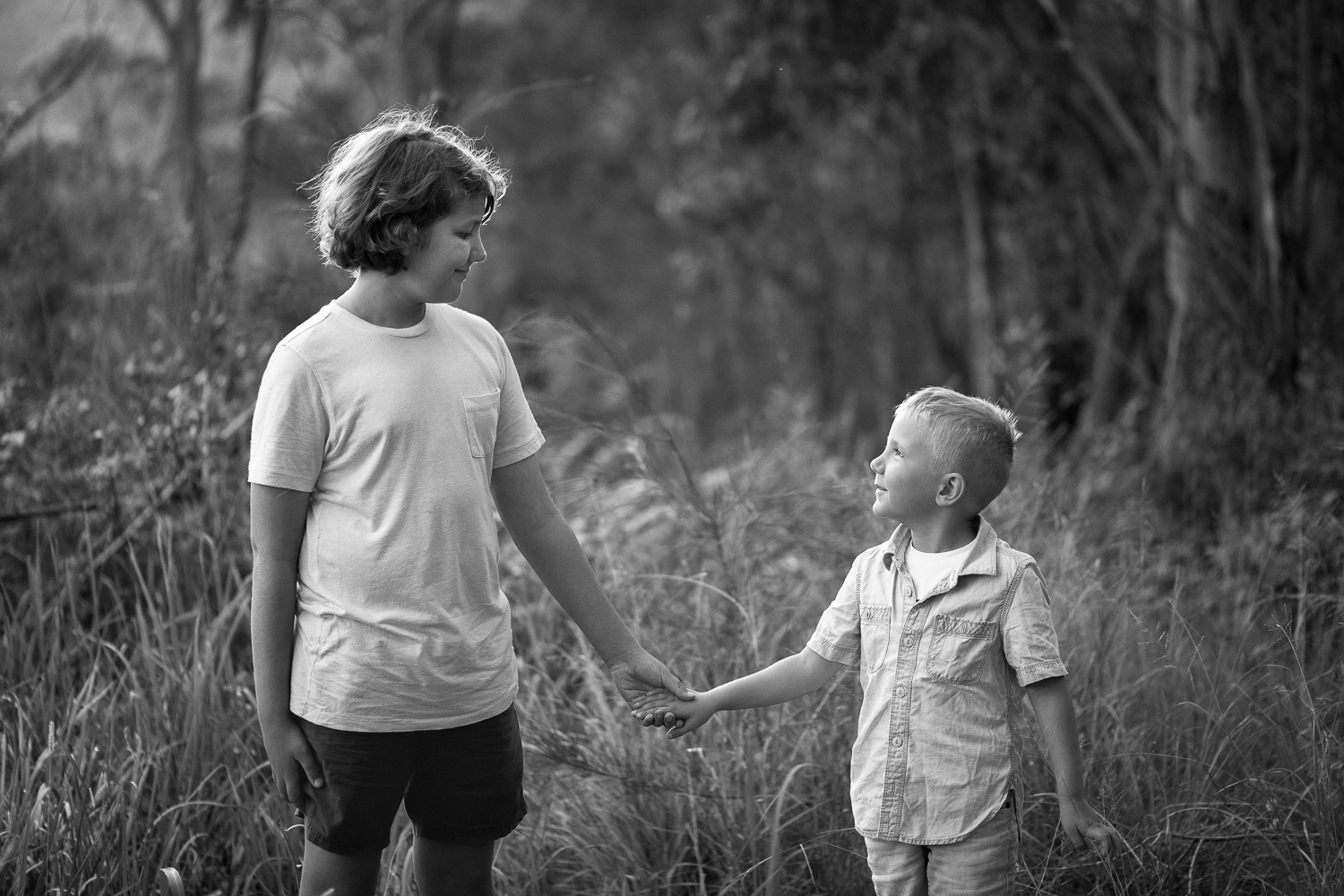 Two young brothers standing in long grass in bushland setting holding hands and looking at each other for natural light authentic children's photography outdoor photo session in Sutherland Shire Sydney