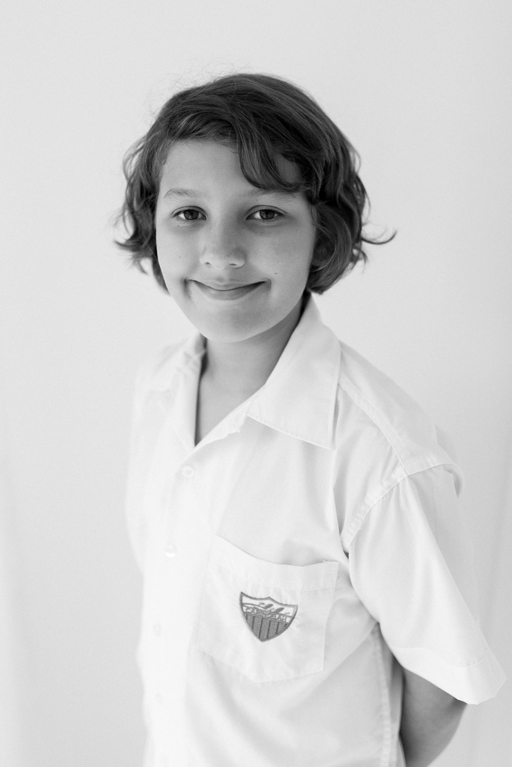 Black and white image of young boy smiling at camera in crisp white shirt ready for first day at selective high school NSW photographed in natural light children's photography studio in Sutherland Shire Sydney
