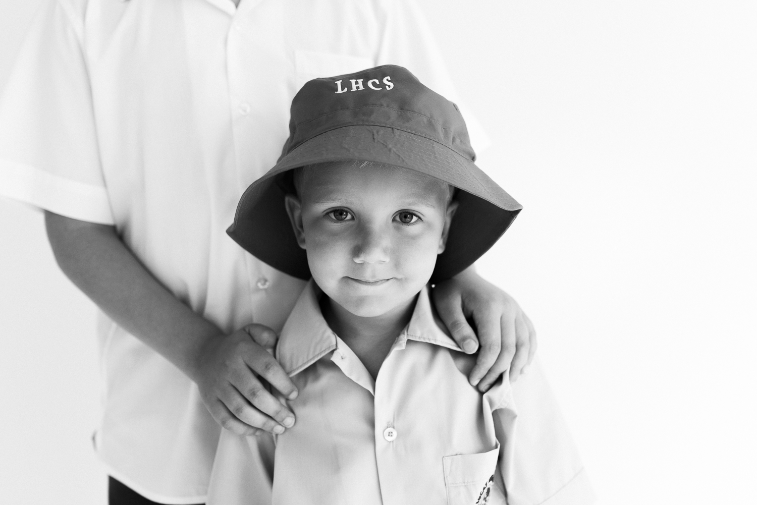 Black and white image of young boy in kindergarten school uniform with big brothers hands on his shoulders, ready to start first day of school and looking confidently at camera, in natural light photography studio for children and families in Sutherland Shire Sydney