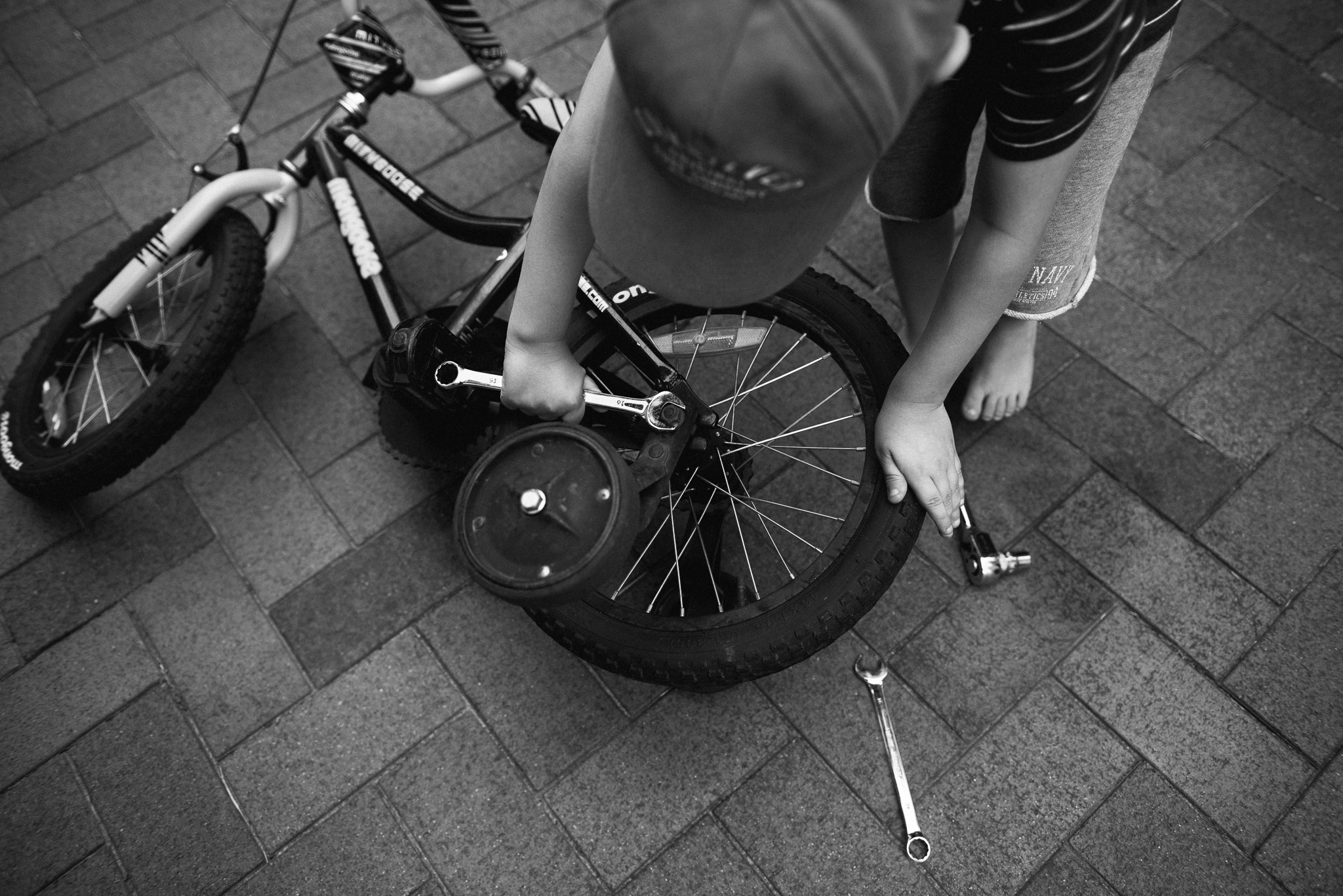 Black and white image of young boy taking training wheels off his bike with a wrench as photographed by Sutherland Shire Childrens Photographer Sevenish Photography