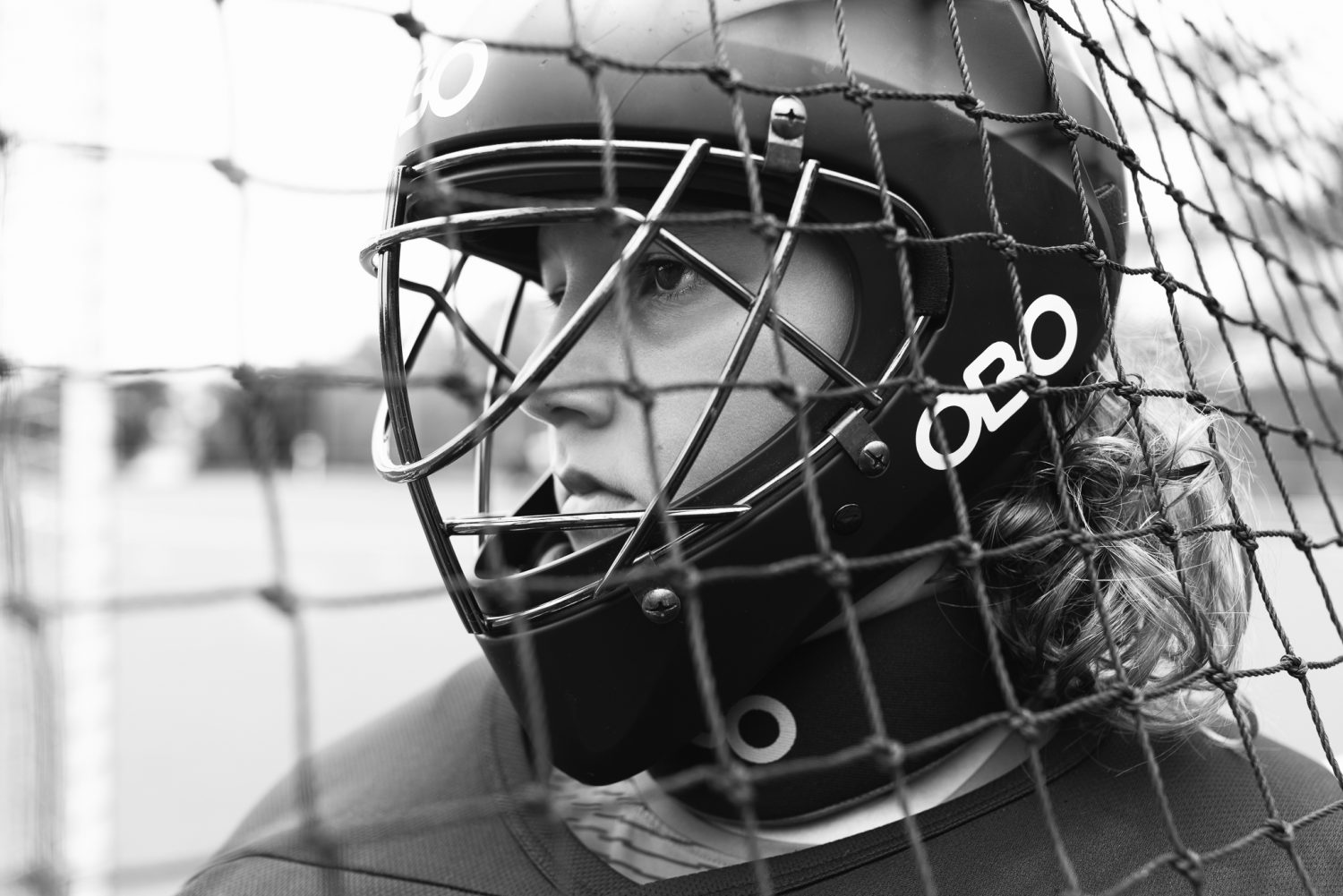Black and white image of young boy in field hockey goalie helmet looking at field as photographed by Sutherland Shire Childrens Photographer Sevenish Photography