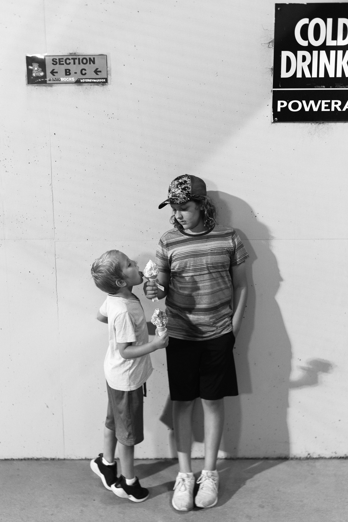 Black and white image of two young brothers eating ice cream and older brother sharing his with younger brother, as photographed by Sutherland Shire Childrens Photographer Sevenish Photography