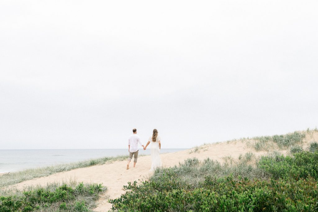 Woman and man walking hand in hand up a sand dune and towards the ocean as photographed by Sutherland Shire Maternity Photographer Sevenish Photography