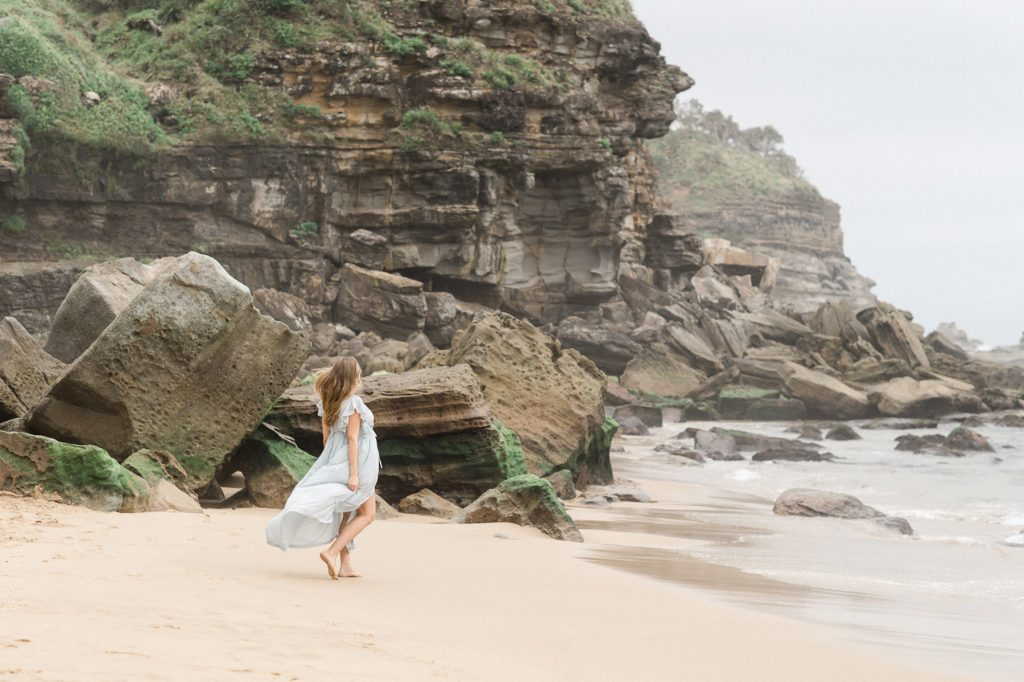 Pregnant woman in pretty blue dress walking towards water with cliffs in background as photographed by Sutherland Shire Maternity Photographer Sevenish Photography
